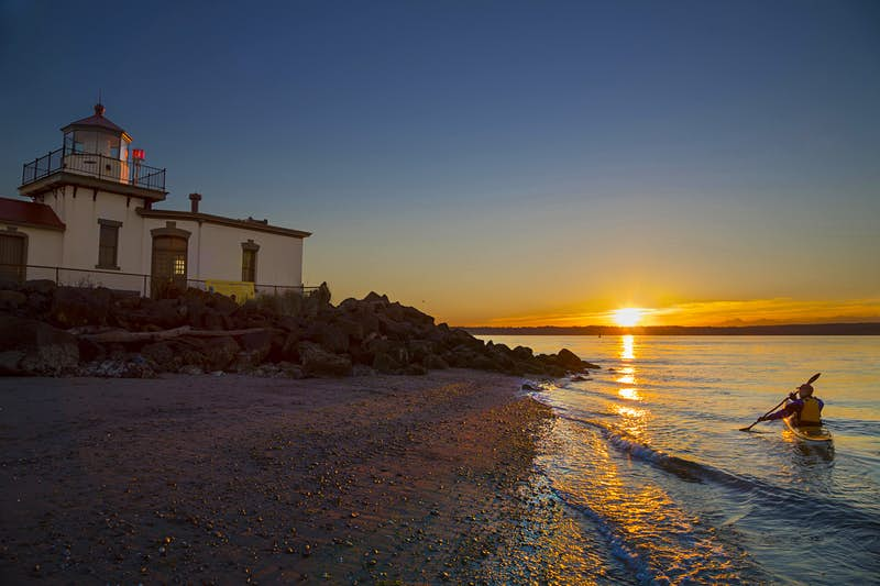 A kayaker takes a sunset trip near the West Point Lighthouse in Discovery Park. Image by Danita Delimont / Gallo Images / Getty