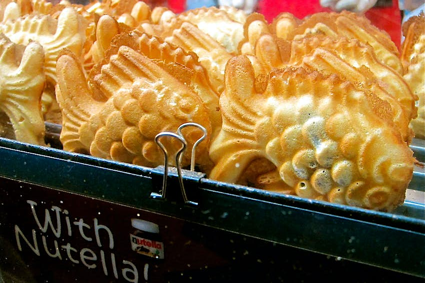 A close up of fish-shaped Nutella-filled waffles in a metal container.