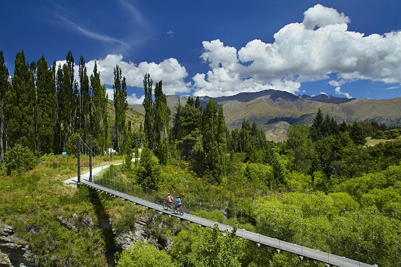 Cyclists crossing a suspension bridge on New Zealand's Arrow River Bridges Trail. Image by Danita Delimont / Gallo Images / Getty Images