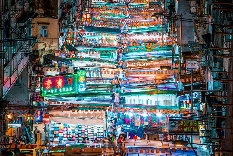 An overhead shot numerous brightly lit shopping stalls in a street market in Mong Kok, Hong Kong.