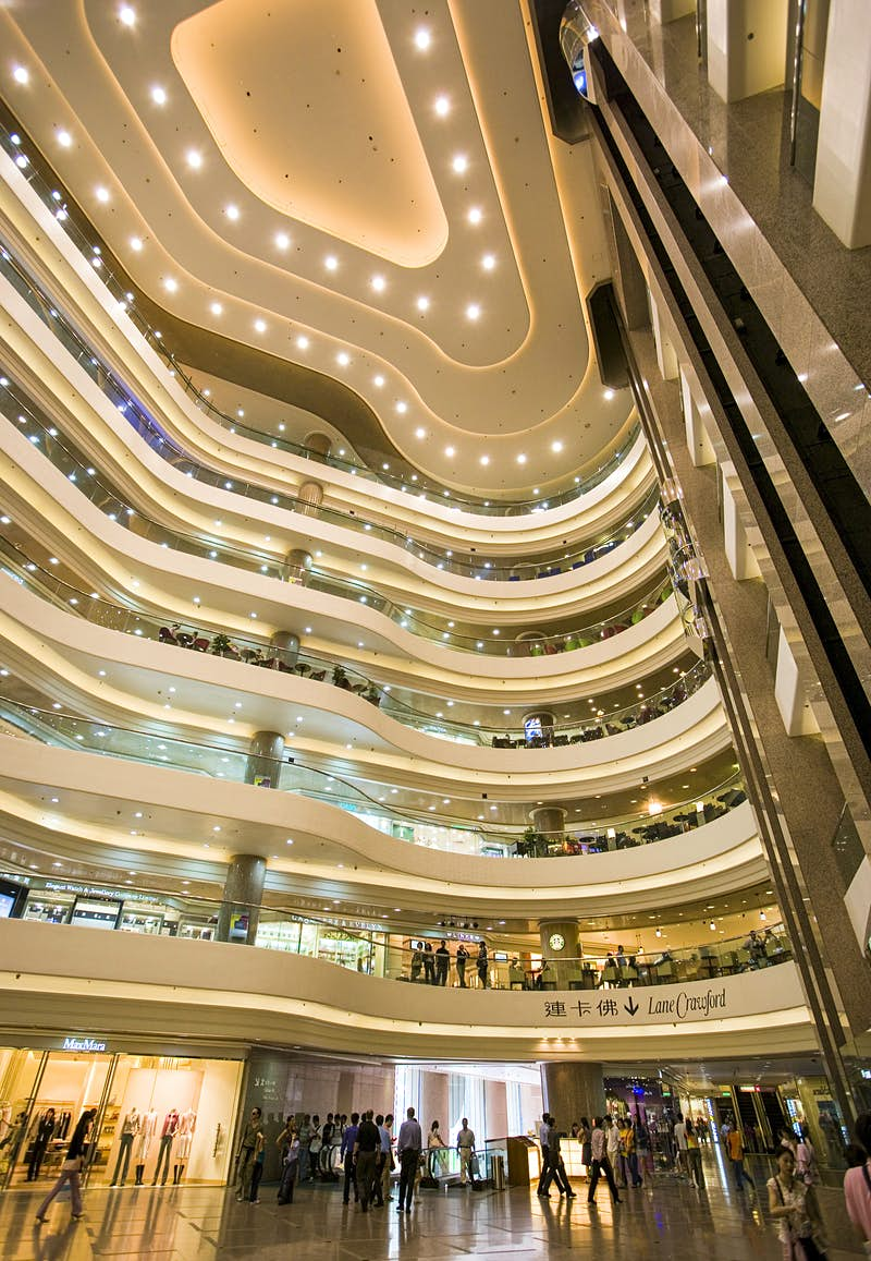 A view of a well-lit, tiered atrium with seven stories at Times Square Mall, Hong Kong.