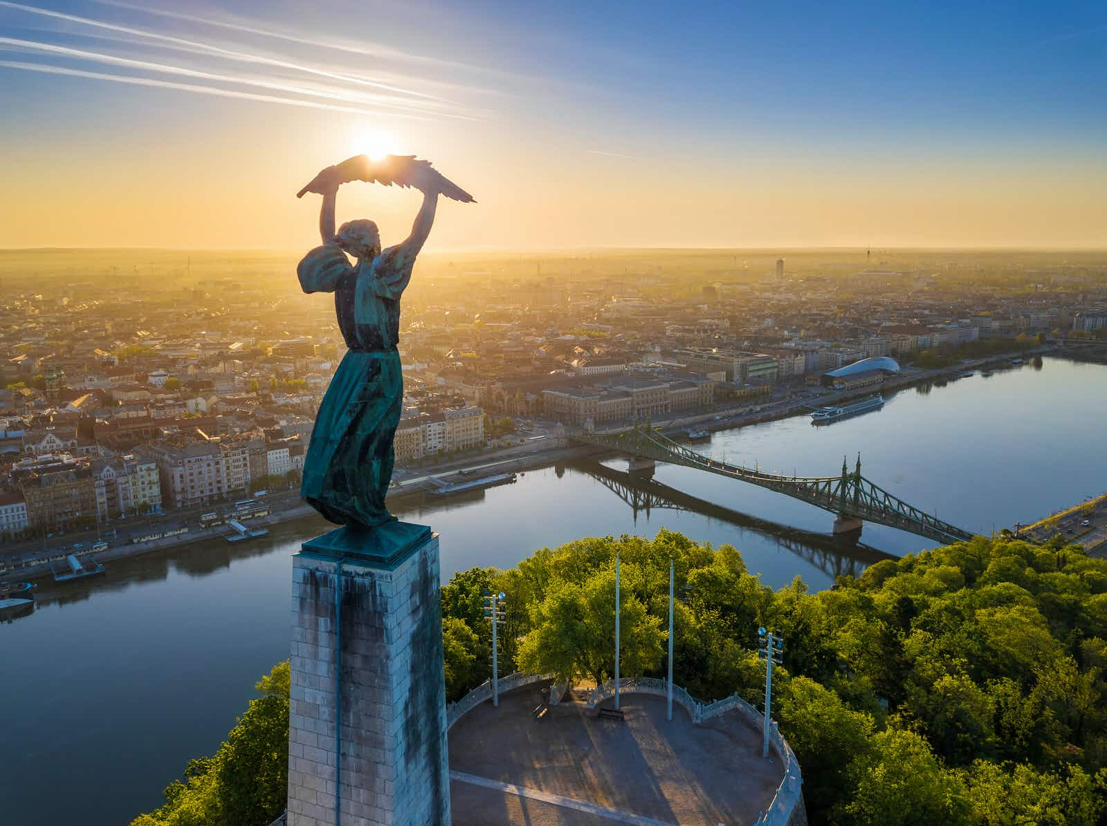 Aerial of the Hungarian Statue of Liberty with Liberty Bridge and the Budapest skyline during sunrise.