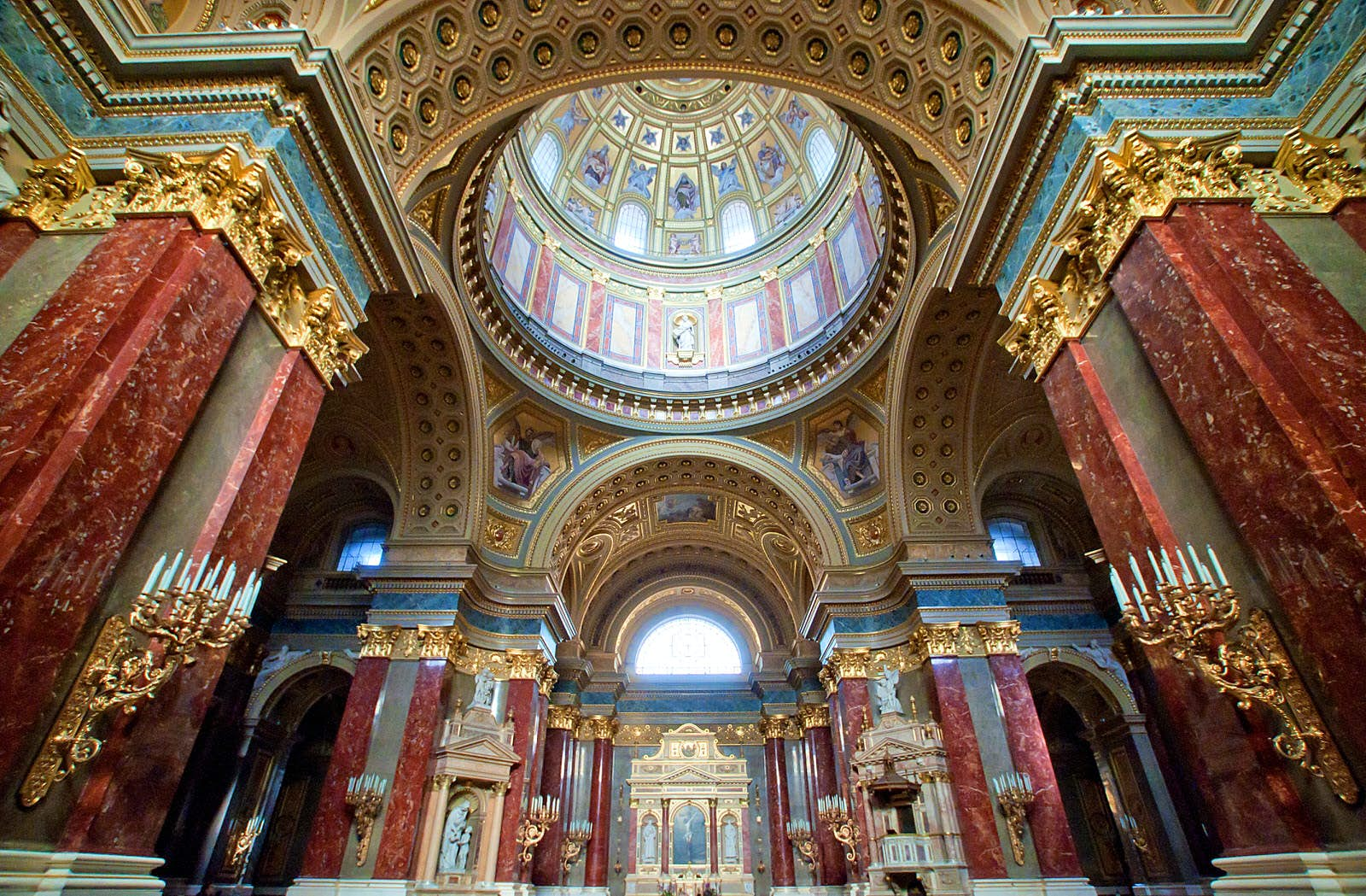 A shot of the ornate interior of the Basilica of St Stephen, showing the red walls, large dome and gold alter among other grand furnishings
