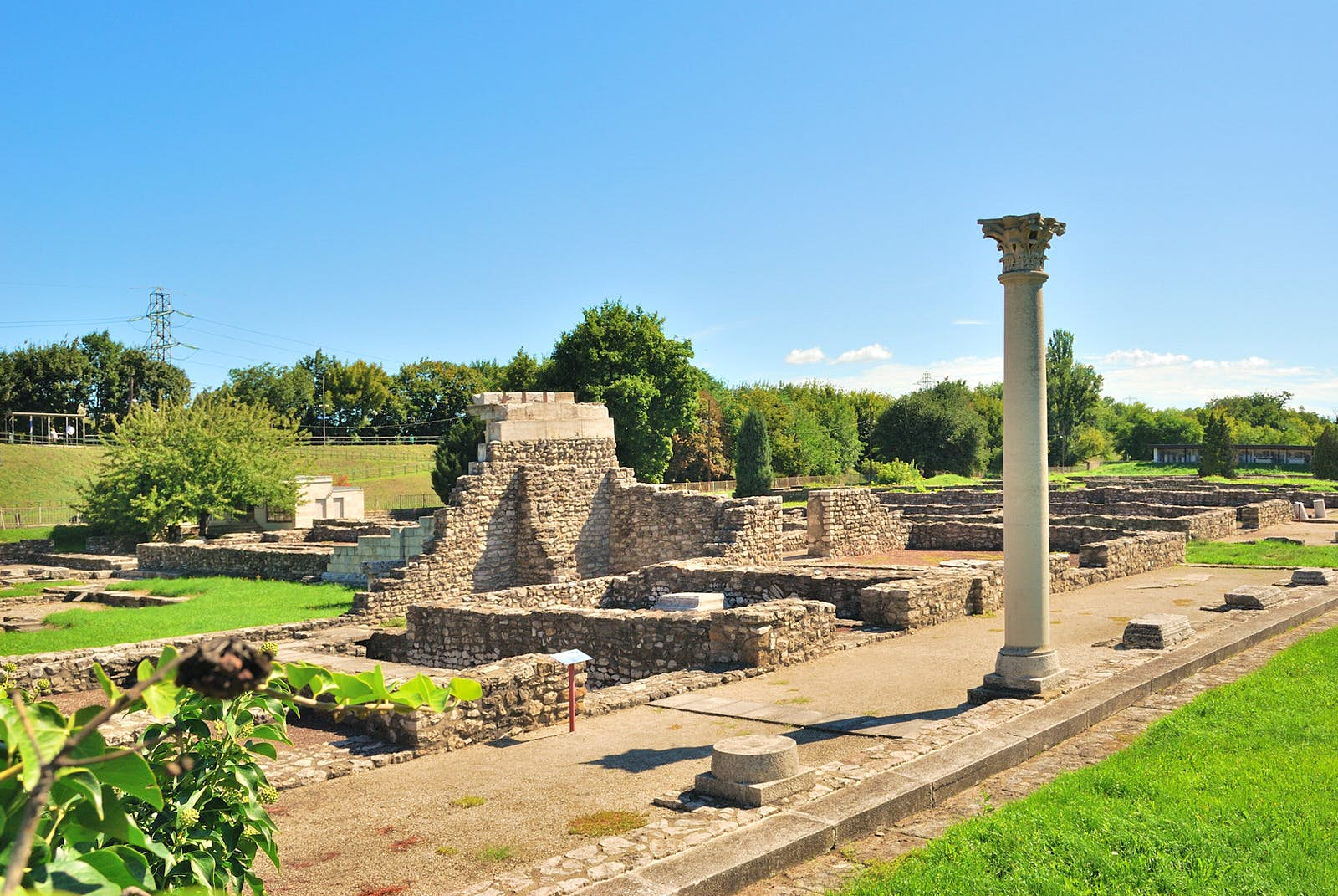 The ruins of the Aquincum Roman baths: a collection of small walls and pillars standing in a green field