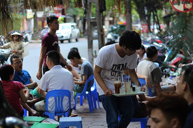 People drinking outside a cafe in Hanoi