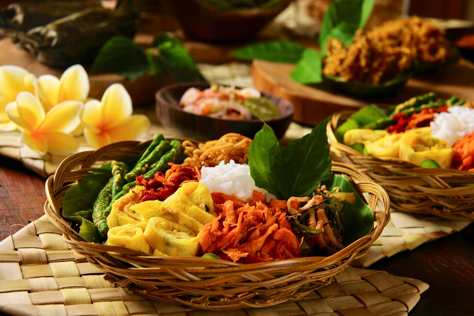 A popular Balinese meal of rice with variety of vegetables in a wooden bowls sitting on a bamboo place mats. Flowers are placed around the bowls of food. Dining in Bali can sometimes look like a work of art.