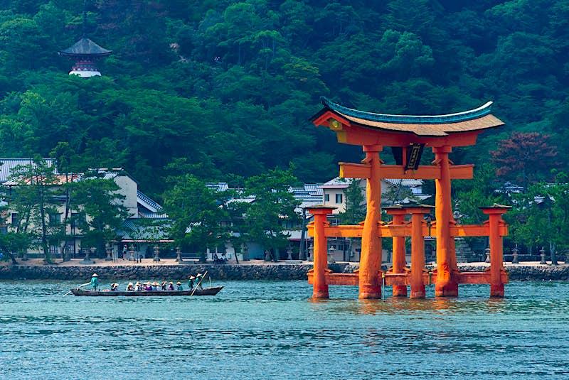 Một chiếc thuyền chèo với 16 người chèo thuyền tiến đến một cổng torii của Nhật Bản, đứng trong nước; những điều tốt nhất để làm trong mùa hè ở Nhật Bản