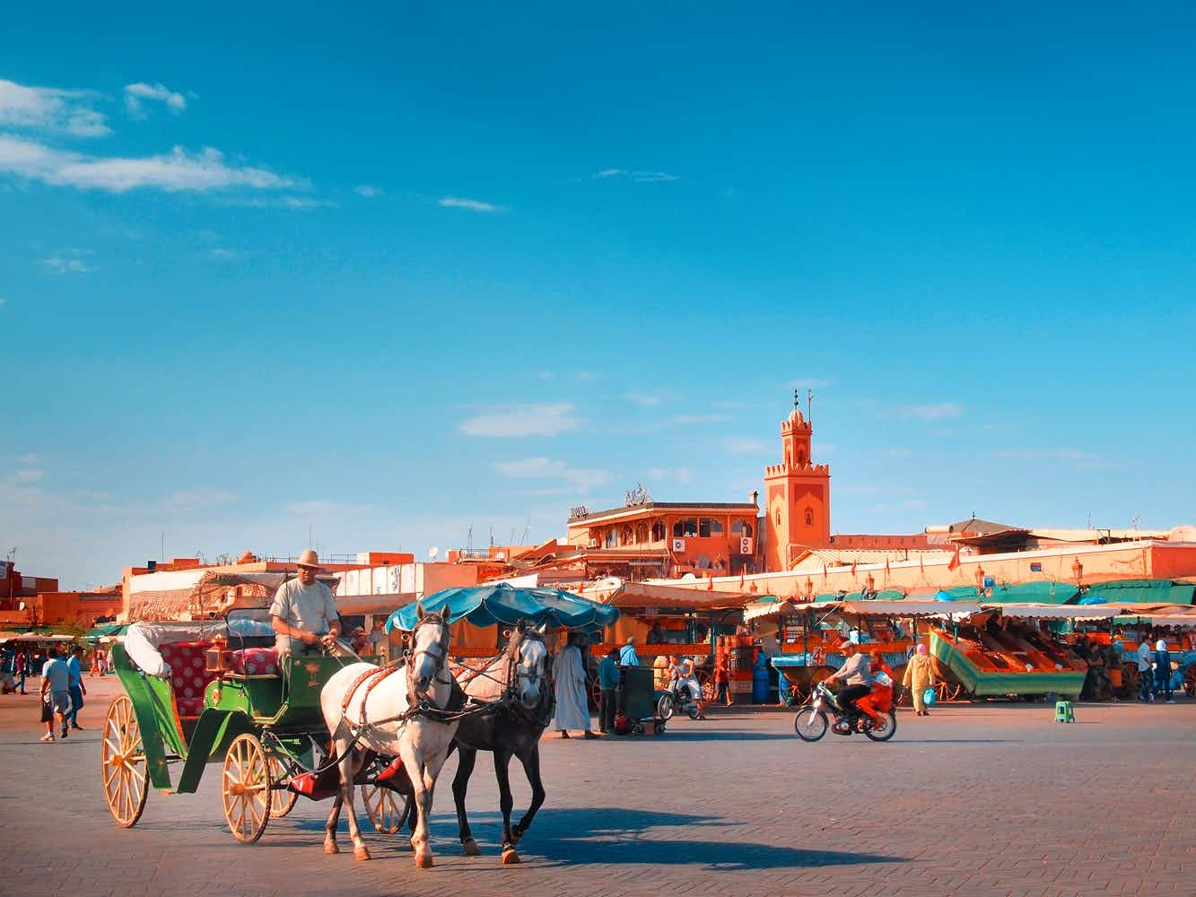 A horse and carriage drive through a sunny Djemaa el-Fna. Image by Alberto Manuel Urosa Toledano/Moment Editorial/Getty Images