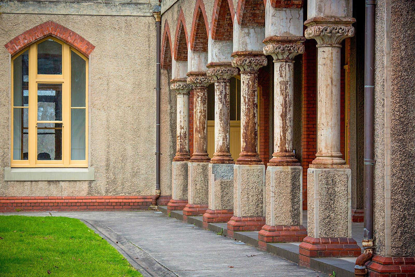 Des piliers en pierre usés bordent une petite pelouse, avec le mur du couvent et une fenêtre cintrée en arrière-plan. Melbourne, Australie.