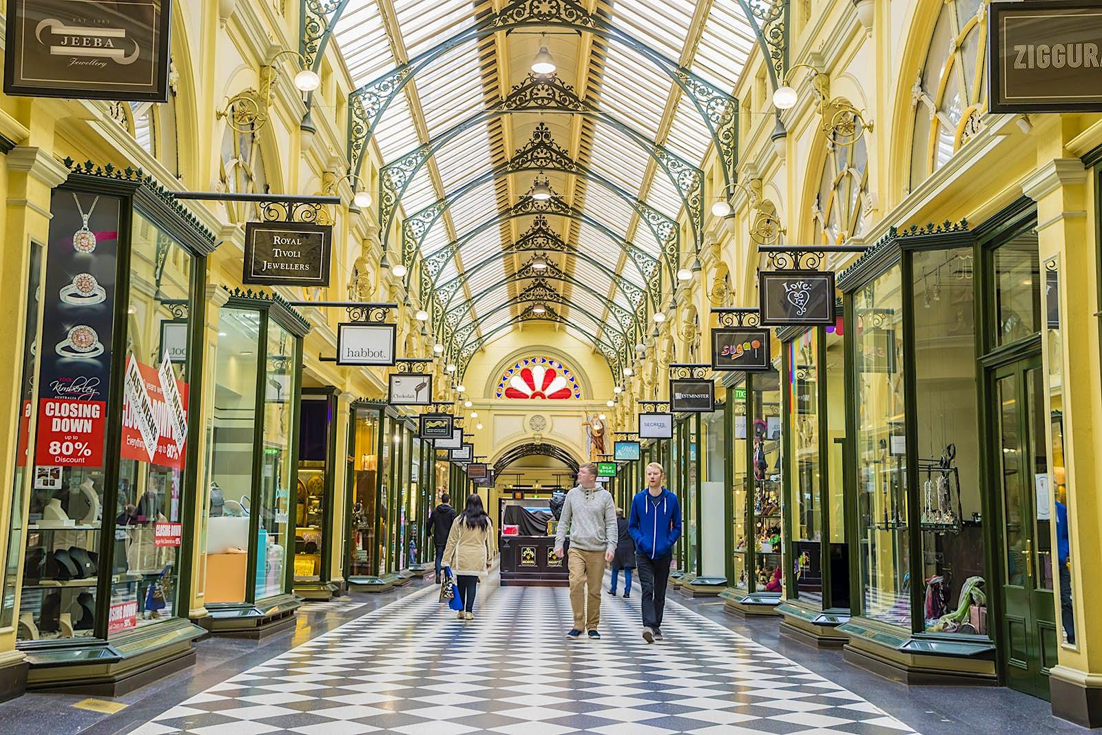 Les gens marchent dans un couloir recouvert de sols marqués. Le plafond est un puits de lumière en verre cintré et les murs sont de couleur or. Melbourne, Australie.