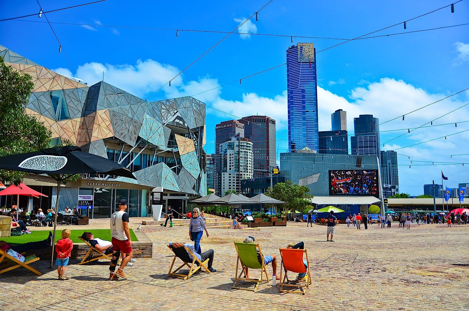 Les touristes sont assis sur des chaises multicolores sur Federation Square. Un bâtiment d'architecture moderne est visible ainsi qu'une ligne d'horizon des tours d'affaires. Melbourne, Australie.