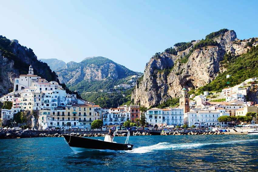 A speedboat travels through the waters with a coastal town on the Amalfi Coast in the background.