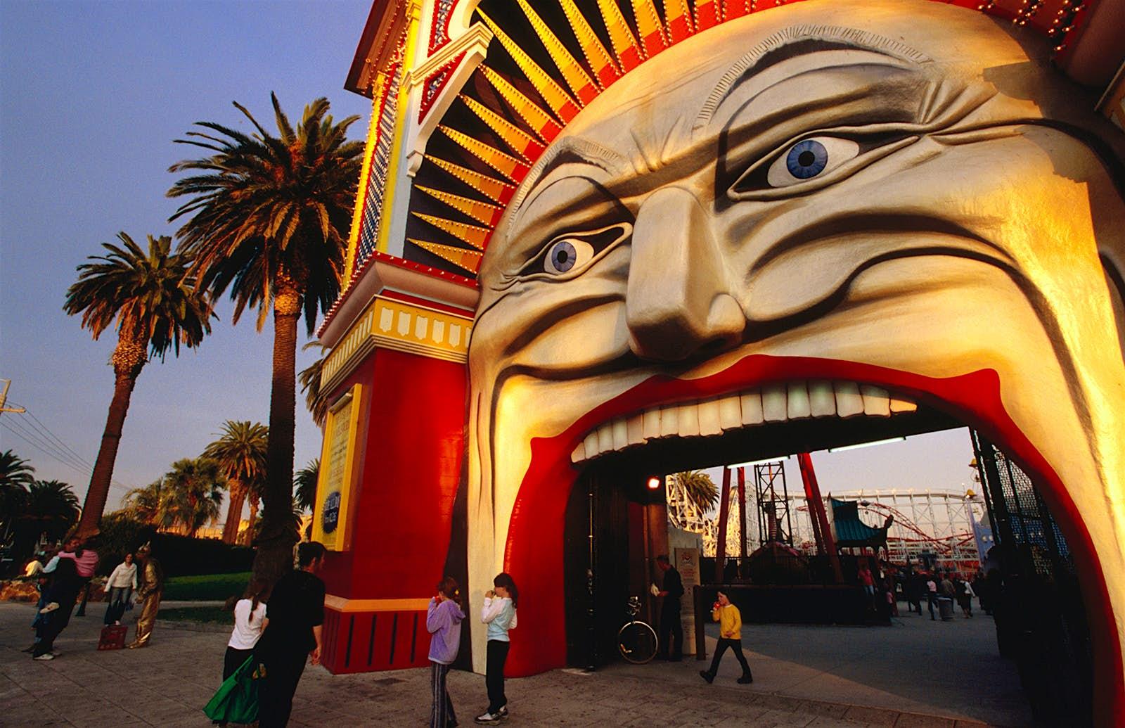 Les gens entrent à l'entrée de Luna Park, qui ressemble à un grand visage qui ouvre la bouche. St Kilda, Melbourne.