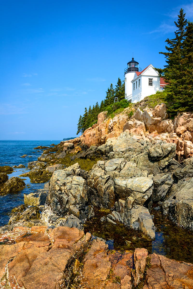 A lighthouse overlooking the rocky coastline of Acadia National Park; the USA's top 10 natural wonders