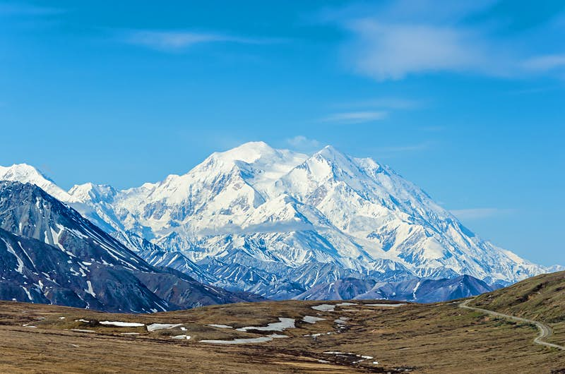 The snowy peak of Denali, with brown tundra below; USA's top natural wonders