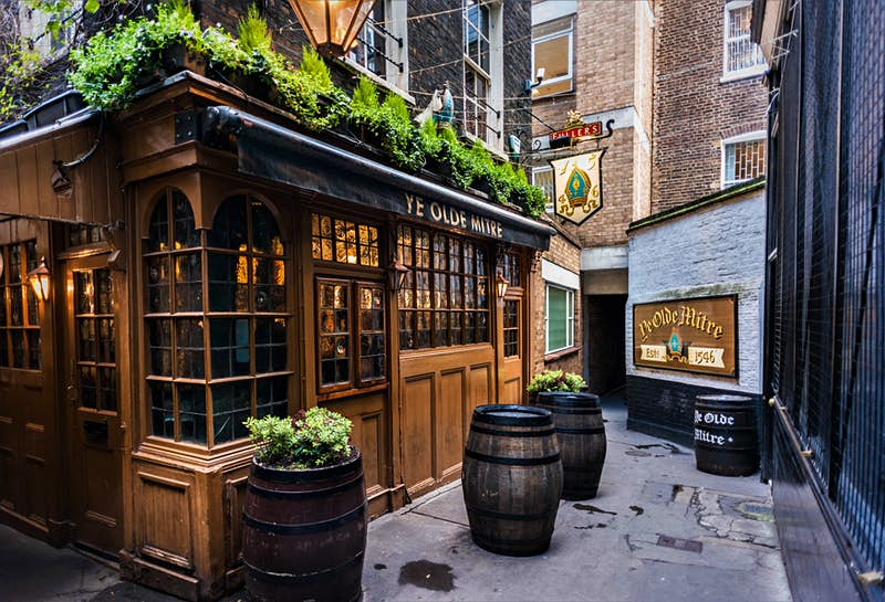 The exterior of Ye Olde Mitre pub, London. The pub has lots of hatched windows and wooden panels. The top of the pub features lots of luscious planters and there is some outdoor seating.