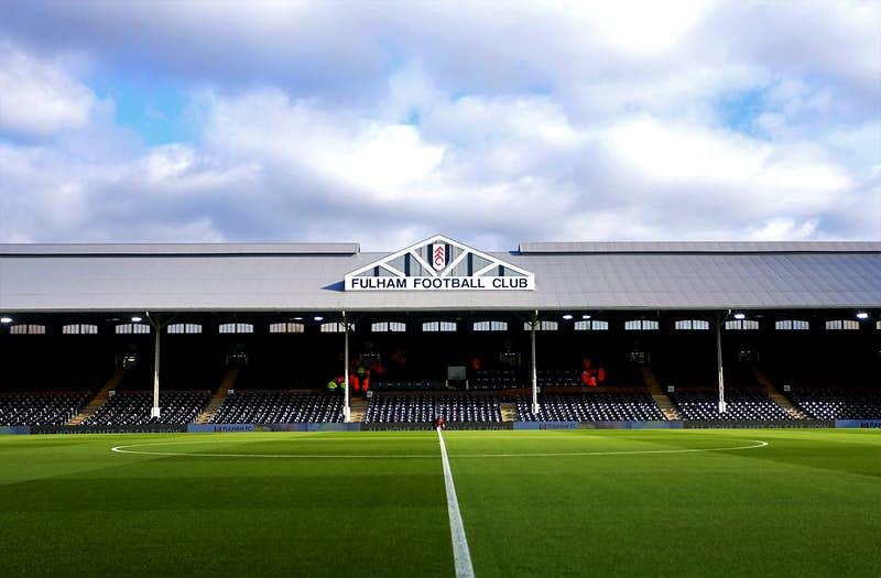 Craven Cottage football ground on a slightly overcast day. The football pitch and stands are empty and the vibrant green grass looks perfect.