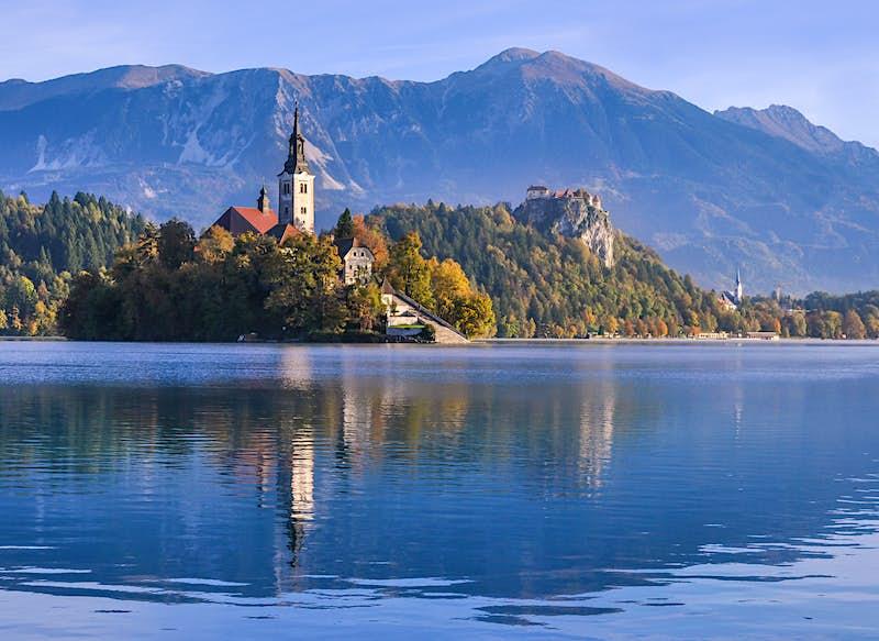 Uma igreja em uma ilha no meio de um lago. Um castelo fica em um afloramento rochoso atrás da ilha, e há montanhas ao longe.