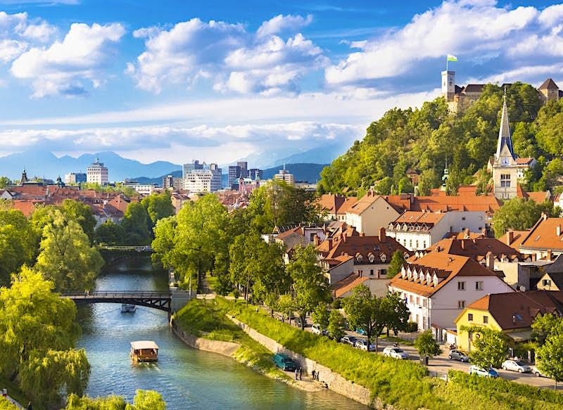 Um rio atravessa uma cidade, com edifícios de telhado vermelho ao longo da margem e um castelo na colina