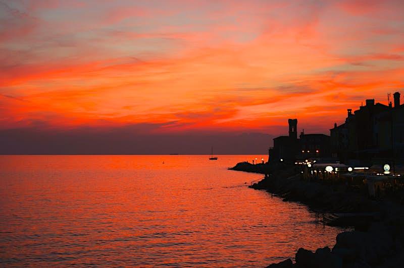 Um céu laranja e roxo é refletido no mar calmo. Edifícios ao longo da costa e um barco no mar aparecem como silhuetas