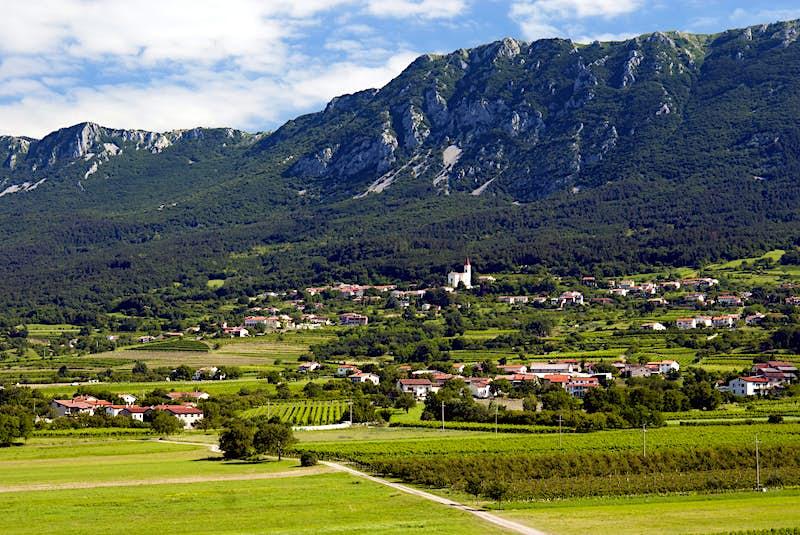 Uma pequena cidade com vinhedos verdes ao redor é cercada por uma grande montanha escarpada