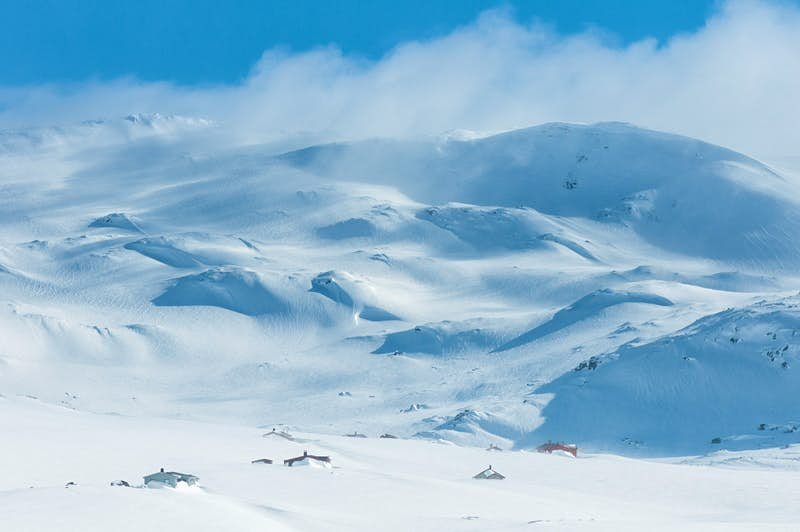 Snow drifts off the top of a range of snow-covered mountains. At the base are small lodgings nestled in the snow