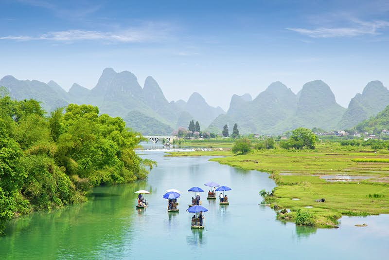 A collection of small boats glide across the river near Guilin. In the distance you can see a range of grass-covered mountains