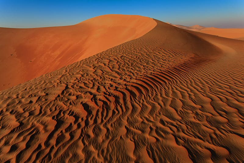 Ripples of sand lead towards the top of a rust-colored dune in the Empty Quarter