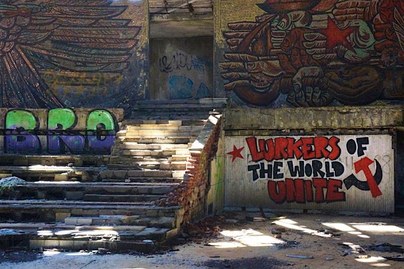 Modern graffiti inside the Buzludzha monument are a parody of communist slogans © Anita Isalska / Lonely Planet