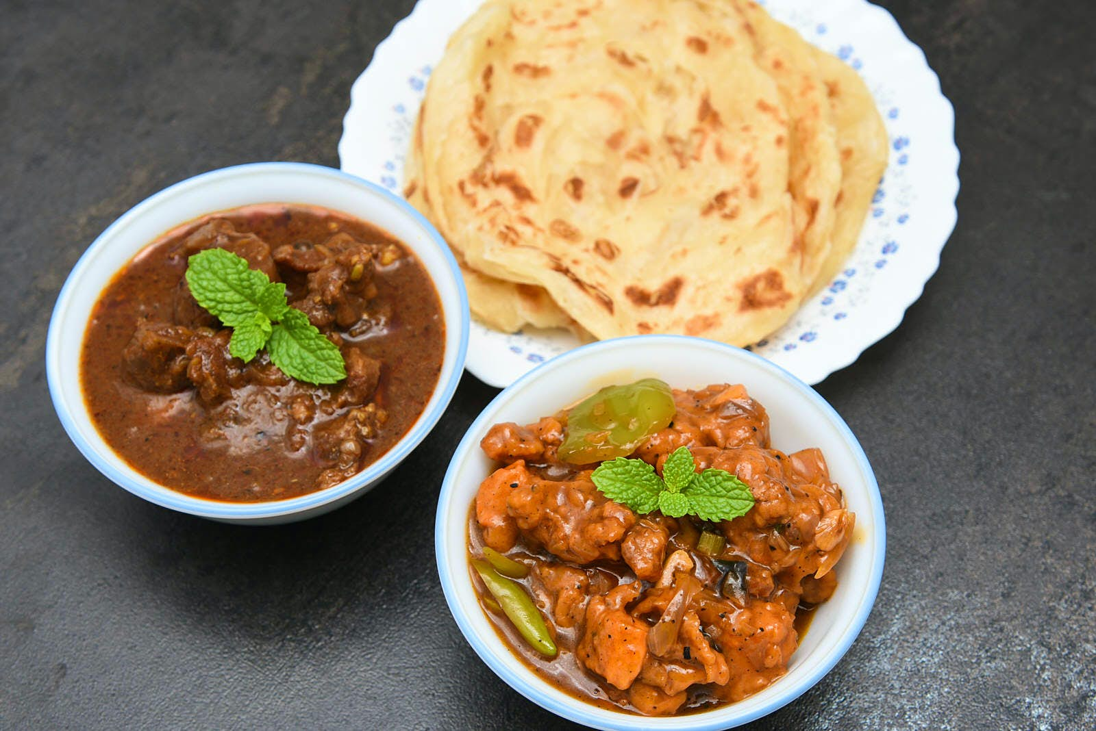 A selection of Indian dishes including beef curry and a plate of chapatis
