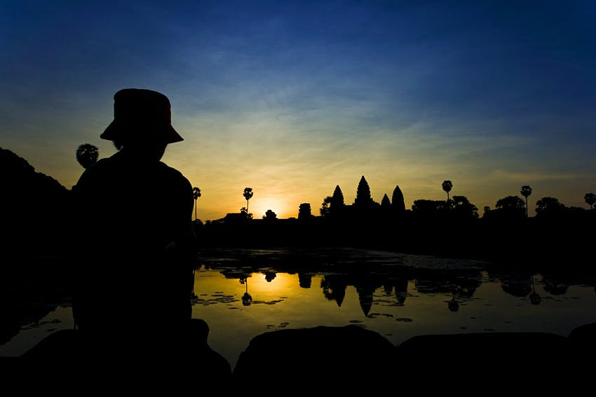 A figure sits in the foreground near the lake watching the sun rise behind the temple of Angkor Wat, which remains in shadow.