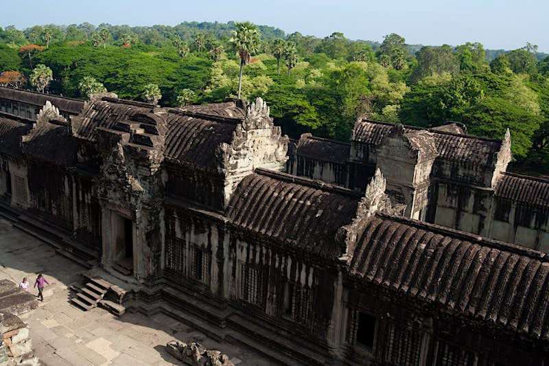 A section of the outer wall at Angkor Wat with thick jungle in the background