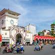 The entrance to the market is a white facade with a clock tower that stands tall against a blue sky. Several motorcycles speed by in the road in front of the market building