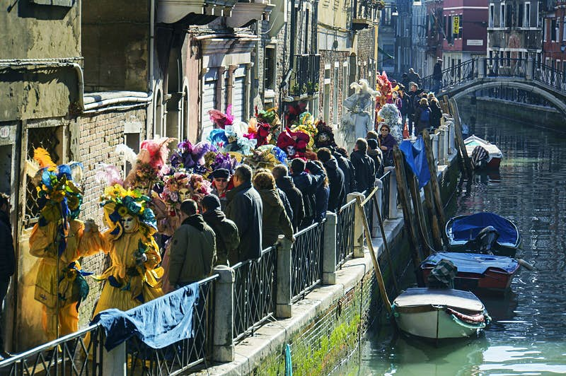 A procession of masked revellers making their way down a canal in Venice