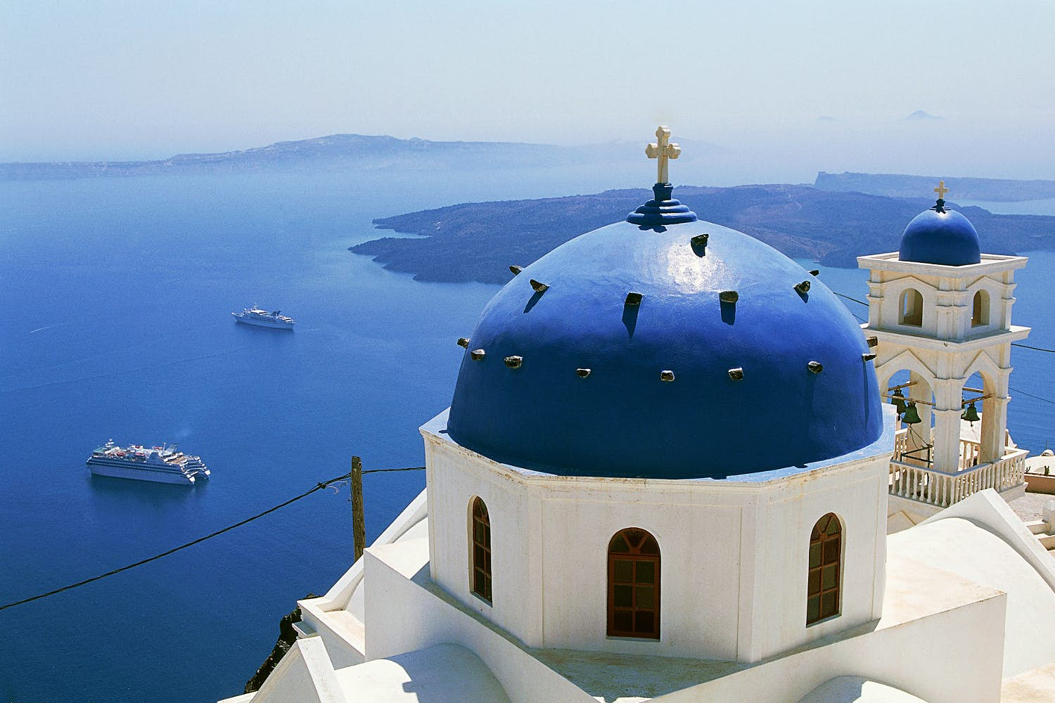 A white church with a blue dome overlooks the ocean in Santorini.