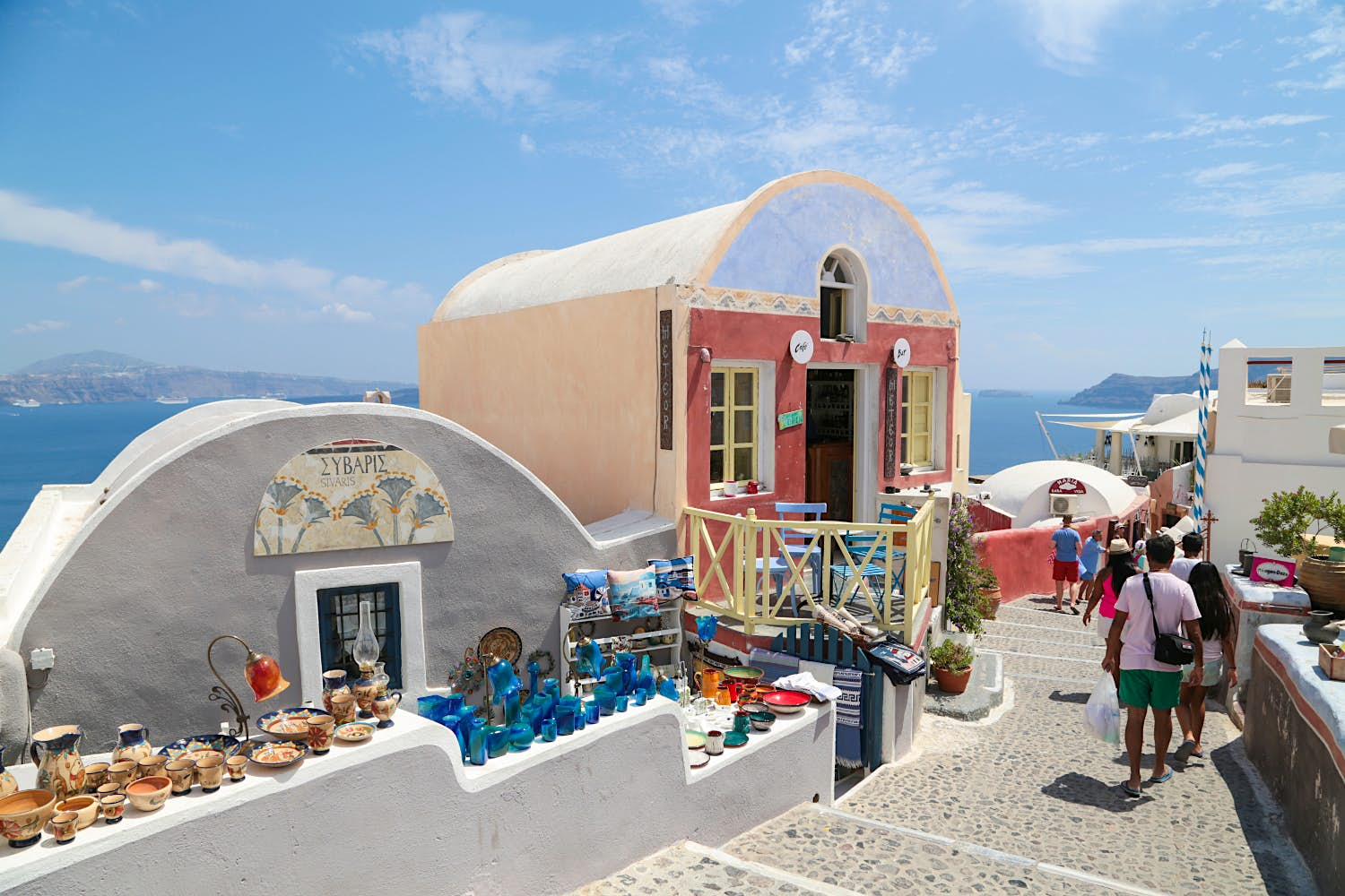 Picturesque alleys of Oia village lined with domed buildings selling souvenirs.