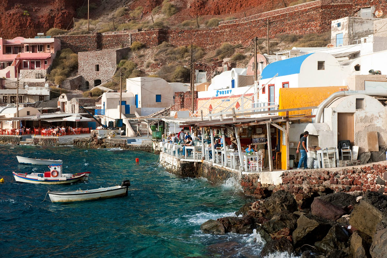 Restaurants with patios line the stone wall at the Ammoudi port.