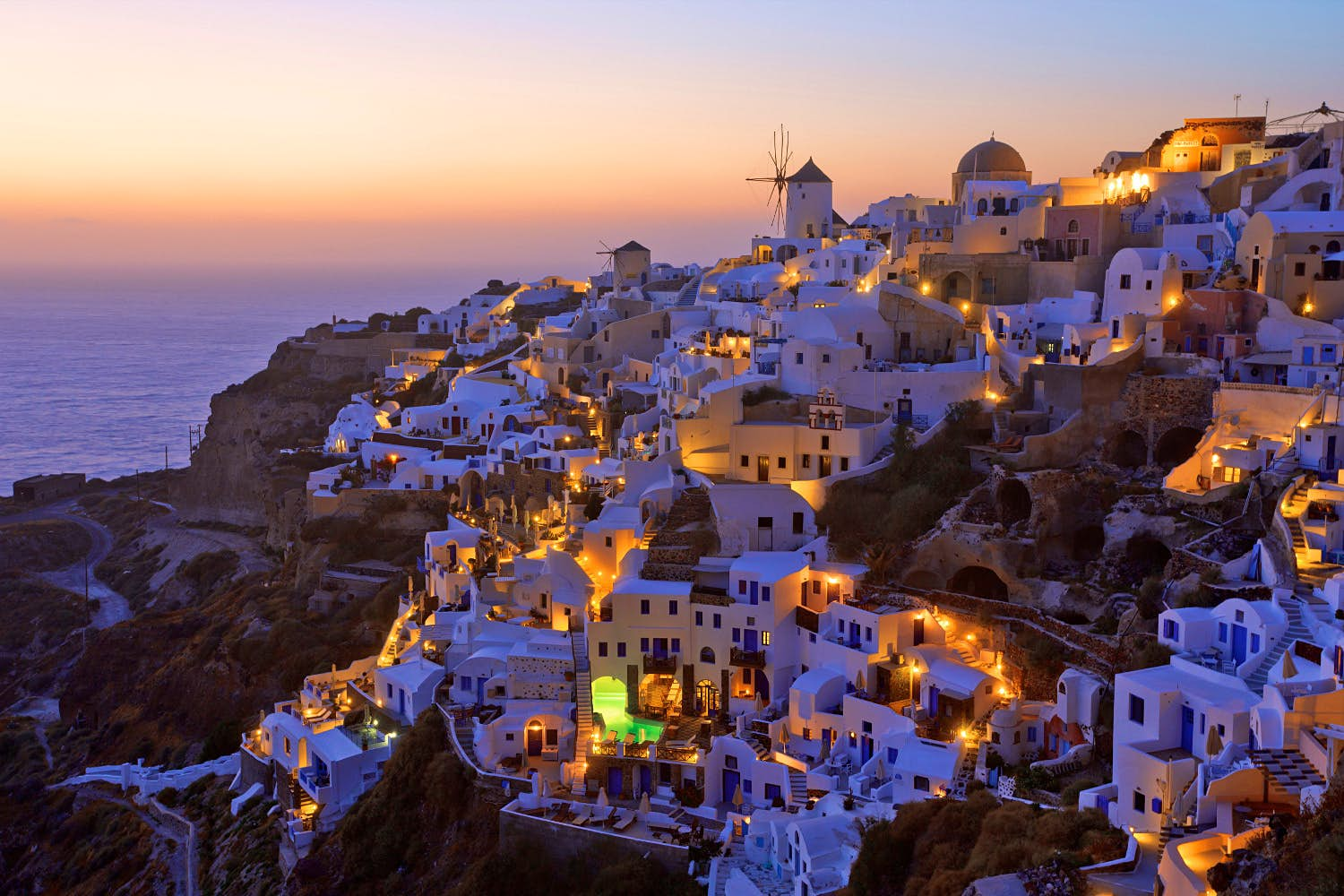 The sky turns pink and purple during sunset over the white buildings of cliffside Santorini.