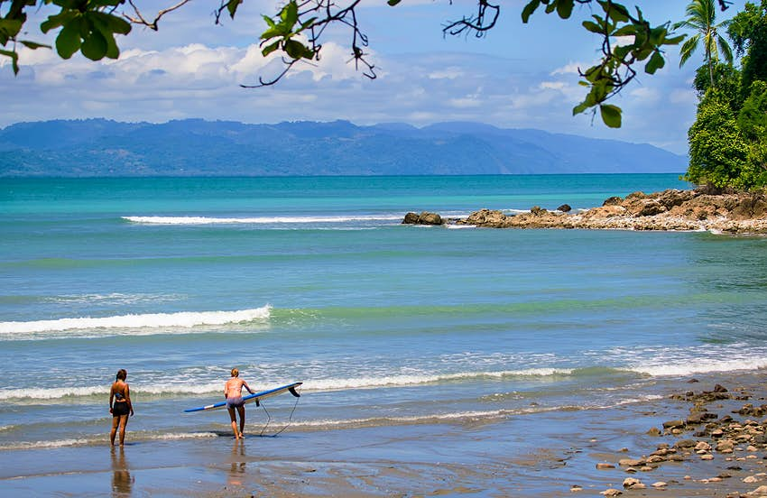 Two surfers on the beach on Osa Peninsula, Costa Rica