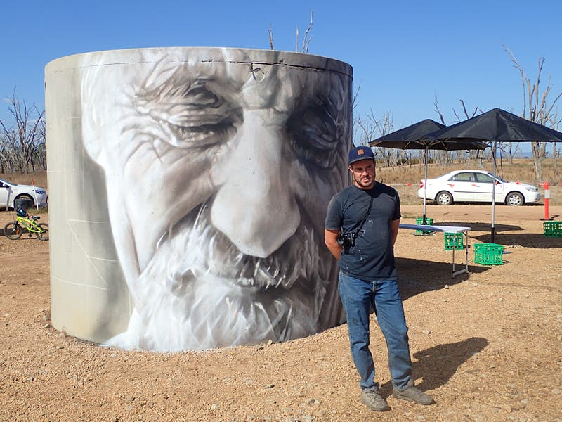 Artist Guido van Helten stands in front of his art in the Winton Wetlands near Benalla. © Tim Richards / Lonely Planet