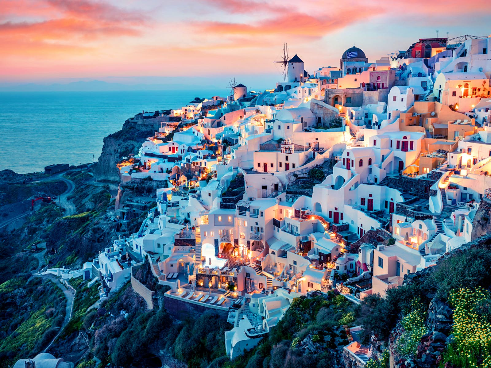 Sunset over the white hillside buildings of village of Oia.