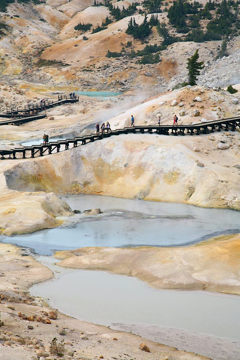 Visitors safety boardwalk among the Mud, ash and sulfur-rich ponds and fumaroles of Bumpass Hell in Lassen Volcanic National Park.