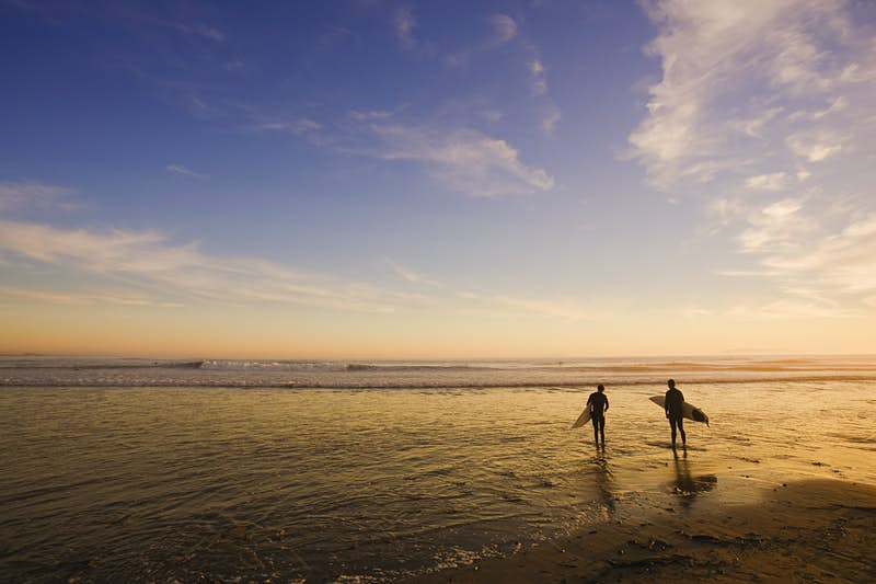 Ttwo surfers entering sea, at sunset and low tide. The surfers are silhouetted against the calm water.