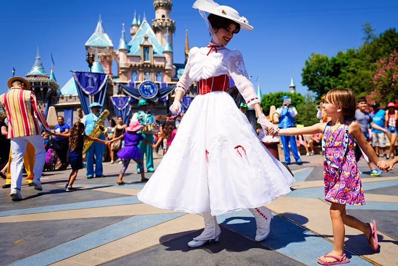 An actor dressed as Mary Poppins smiles at a young child as she leads a line of children in song and dance in front of Cinderella's castle during Disney's 60th Diamond Celebration.