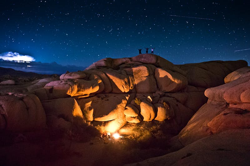Campers are seen on top of large rocks at night while a fire illuminates their campsite in Joshua Tree National Park, California.