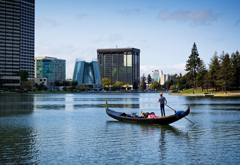 Gondola cruises across a glass lake with the Oakland skyline in the background
