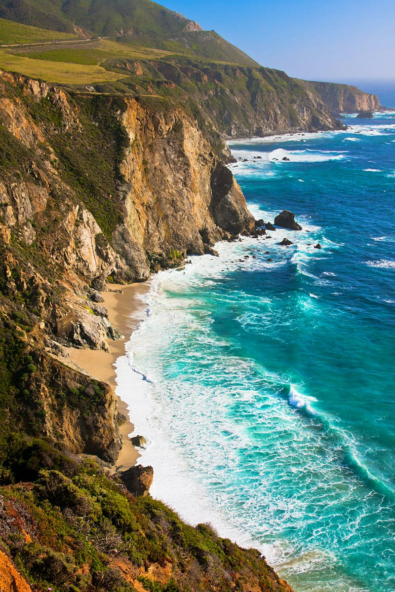 Big Sur's coastline. Cliffs with shrubbery and exposed rock face plunge down to meet a rough, blue sea. A road winds along the top of the cliff.