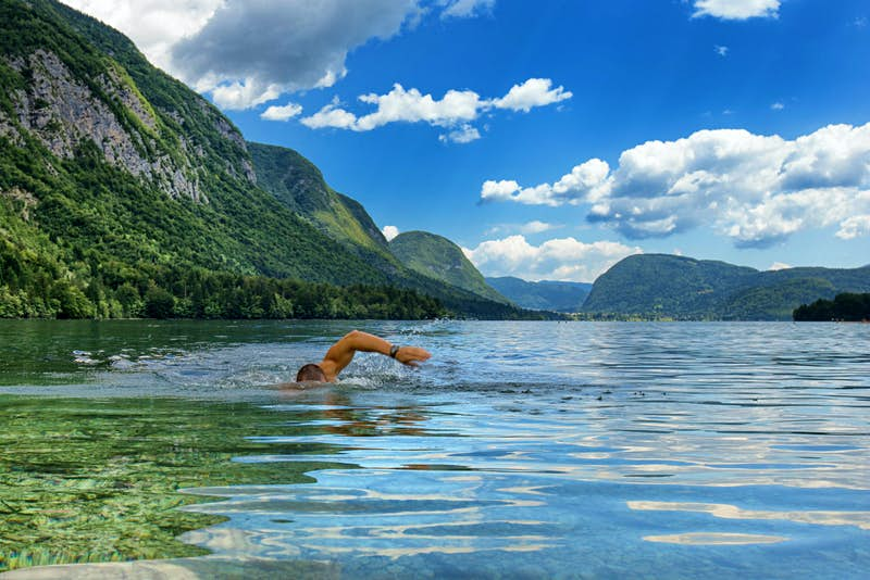 A man swims through the waters of Lake Bohinj, with mountains in the background and a cloudy blue sky overhead