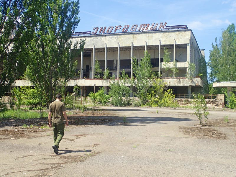 A guide walks across tarmac towards the derelict Palace of Culture in Pripyat; tress are growing in front of and within the pillared concrete structure, which has a large sign in Ukrainian script on its roof.