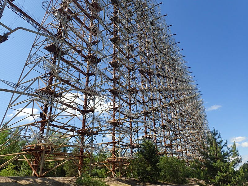 Abandoned radar installation in the Chornobyl Exclusion Zone, resembling a huge scaffolding unit made of lots of grey pipes and brown pillars.